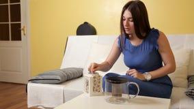 Ein junges Mädchen gießt Tee in eine Teekanne für das Schweißen Die chinesische Teekanne des Lehms, zwei Cup und Zucker auf einer stock video