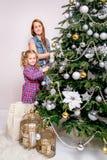 Ein junges Mädchen hilft ihrer Mutter, den Familie Weihnachtsbaum zu verzieren lizenzfreie stockbilder