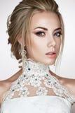 Ein junges Mädchen im Bild einer Braut in einem Hochzeitskleid und in schönen glänzenden Ohrringen Ein schönes Modell mit einem h Lizenzfreie Stockbilder