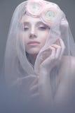 Ein junges Mädchen im Bild einer Braut mit einem Schleier auf ihrem Gesicht Schönes Modell mit einem Kranz von Blumen auf ihrem K Stockfoto