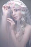 Ein junges Mädchen im Bild einer Braut mit einem Schleier auf ihrem Gesicht Schönes Modell mit einem Kranz von Blumen auf ihrem K Lizenzfreie Stockfotografie