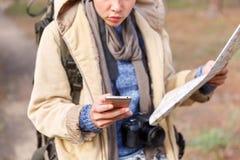 Ein junges Mädchen im Wald sucht nach einer Straßenkarte und benutzt ein Telefon lizenzfreie stockfotografie