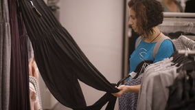 Ein junges Mädchen kleidete in einem blauen T-Shirt an und grauer Rucksack auf zurück zu wählen zwischen grauem, violettem und sc stock video