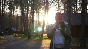 Ein junges Mädchen macht ein Foto, auf einem Hintergrund eines Walddorfs und des schönen Sonnenuntergangs Zeitlupe, 1920x1080, vo stock footage