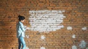 Ein junges Mädchen malt eine Backsteinmauer in ihrem Haus mit einer Rolle Malereiwände mit einer Rolle Malen Sie die bloßen Wände stock video