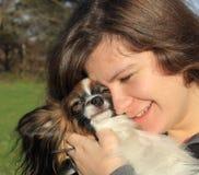 Ein junges Mädchen mit dem langen braunen Haar hält einen kleinen Pelzhund - ihr Haustier stockfotografie
