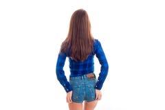 Ein junges Mädchen mit dem langen Haar in den kurzen Hosen eines blauen Hemdes und des Denims wert das Drehen Ihr zurück zu der K Lizenzfreie Stockfotografie