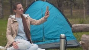 Ein junges Mädchen mit dem langen Haar sitzt nahe einem blauen Zelt im Wald und nimmt ein selfie am Telefon stock video
