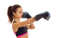 Ein junges Mädchen mit dem Pferdeschwanz blickt in Richtung und erreicht heraus seine Hände vorwärts in den Boxhandschuhen Lizenzfreies Stockbild