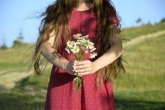 Ein junges Mädchen mit dem schönen Haar in einem roten Kleid, das ein bouque hält Lizenzfreies Stockfoto