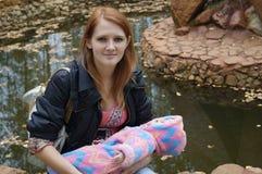Ein junges Mädchen mit einem Baby Lizenzfreie Stockfotos