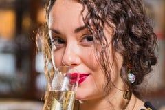 Ein junges Mädchen mit einem Glas Wein in einer schönen Einstellung Stockbild