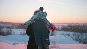 Ein junges Mädchen mit einem Kind, das in Winter Park spielt Wege in der Frischluft Sonnenuntergang stock video footage