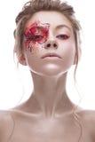 Ein junges Mädchen mit einem kreativen Make-up in Form einer Rotgoldblume auf ihrem Auge Schönes Modell im Bild einer Frühlingsbl Stockfotografie