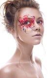 Ein junges Mädchen mit einem kreativen Make-up in Form einer Rotgoldblume auf ihrem Auge Schönes Modell im Bild einer Frühlingsbl Lizenzfreie Stockfotos