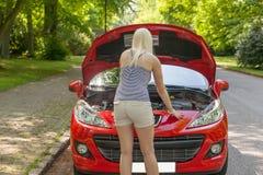 Ein junges Mädchen mit einem roten Auto lizenzfreie stockfotos