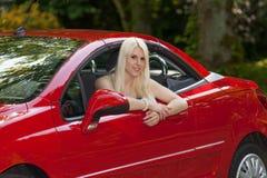 Ein junges Mädchen mit einem roten Auto Stockfotografie