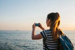 Ein junges Mädchen mit einem Rucksack stellt am Telefon eine schöne Ansicht des Meeres und des Sonnenuntergangs dar Bild für Gedä Stockfotografie
