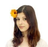 Ein junges Mädchen mit einer Blume in ihrem Haar Stockfoto