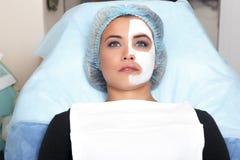 Ein junges Mädchen mit einer Maske der Creme auf dem Gesicht lizenzfreies stockbild