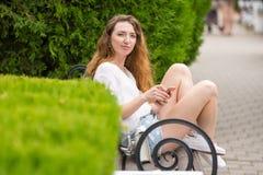 Ein junges Mädchen mit Telefon in ihren Händen, sitzt auf einer Bank im Park und betrachtet dem Rahmen Lizenzfreies Stockbild