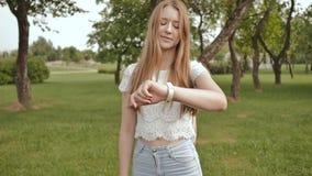 Ein junges Mädchen nimmt an einem Weg im Park teil, betrachtet eine intelligente Uhr auf ihrem Arm und empfängt ein Impulsmaß stock video footage