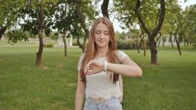 Ein junges Mädchen nimmt an einem Weg im Park teil, betrachtet eine intelligente Uhr auf ihrem Arm und empfängt ein Impulsmaß stock footage