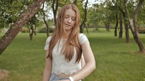 Ein junges Mädchen nimmt an einem Weg im Park teil, betrachtet eine intelligente Uhr auf ihrem Arm und empfängt ein Impulsmaß stock video