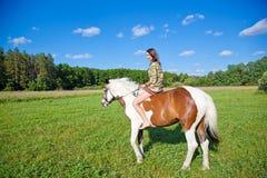 Ein junges Mädchen reitet ein Farbenpferd Lizenzfreie Stockfotografie