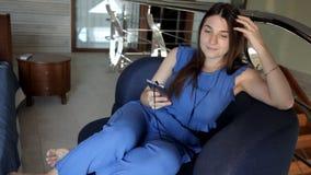 Ein junges Mädchen sitzt auf der Couch, hört Musik auf Kopfhörern und singt stock video footage