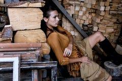Ein junges Mädchen sitzt auf einem Stuhl vor dem hintergrund der Bretter und der Klotz, Lizenzfreie Stockbilder