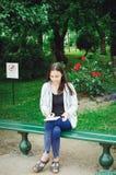 Ein junges Mädchen sitzt auf einer Bank im Garten und zeichnet lizenzfreie stockfotografie