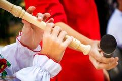 Ein junges Mädchen spielt eine hölzerne Flöte Ausführung eines musikalischen composit stockbilder