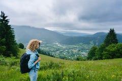 Ein junges Mädchen steht auf einen Berg im wolkigen Wetter die Ansicht genießend Lizenzfreies Stockfoto