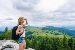 Ein junges Mädchen steht auf einen Berg im wolkigen Wetter die Ansicht genießend Stockfotos