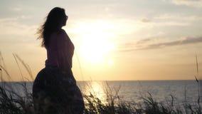 Ein junges Mädchen steht das Meer bereit, das einen schönen Sonnenuntergang betrachtet 4k, 3840x2160 HD stock video footage
