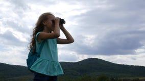 Ein junges Mädchen steht gegen einen Hintergrund von den Bergen und von bewölktem Himmel, die nach Richtungen suchen stock video
