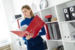 Ein junges Mädchen steht im Büro nahe dem Schutz und hält einen Ordner mit Dokumenten in ihren Händen Lizenzfreie Stockbilder