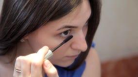 Ein junges Mädchen steht vor Augen einer Schminkspiegelmalerei mit Wimperntusche stock video