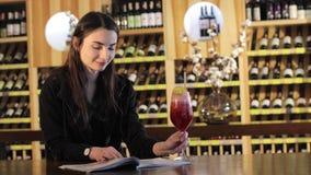 Ein junges Mädchen trinkt ein Cocktail auf einer Tabelle in einem Moderestaurant, junges Mädchen mit einem roten exotischen Cockt stock video footage