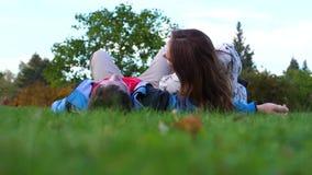 Ein junges Mädchen und ein Kerl, die auf dem Rasen liegen stock video