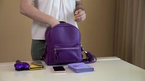 Ein junges Mädchen verbreitet heraus den Inhalt ihrer Tasche auf der weißen Tabelle Inhalt der Damentasche stock footage
