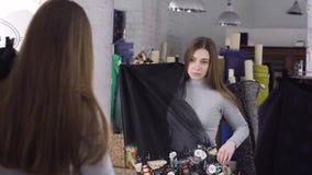 Ein junges Mädchen wählt einen Stoff für ein Kleid nahe einem Spiegel im Atelier stock footage