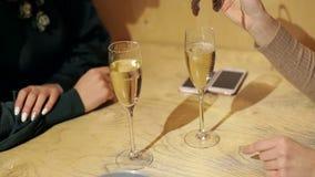Ein junges Mädchen wirft etwas Eis in einem Glas Champagner stock video footage