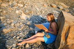 Ein junges Mädchen zeichnet auf das Papier, das auf dem steinigen Ufer bei Sonnenuntergang sitzt Lizenzfreies Stockbild