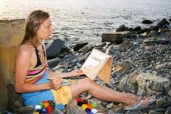 Ein junges Mädchen zeichnet durch Gouache auf dem Papier, das auf dem steinigen Seestrand bei Sonnenuntergang sitzt Stockfotografie