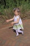 Ein junges Mädchen zeigt Glück, während sie den Anblick an einem allgemeinen Garten erforscht Lizenzfreies Stockbild