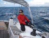 Ein junges Mädchen zieht die Linien hoch, um den Reißnagel auf einer Segeljacht zu ändern Segelnregatta auf dem adriatischen Meer stockfotos