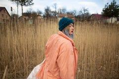 Ein junges M?dchen, das einen Pastellmantel und einen stilvollen Hut tr?gt, wirft auf einem Weizengebiet auf Hinteres viev stockfotografie