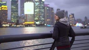 Ein junges M?dchen in einer schwarzen Jacke und in einem Hut betrachtet den Anblick von Shanghai auf der Ufergegend des Vaitan stock footage